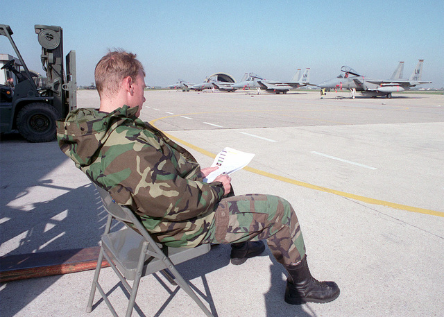 SENIOR AIRMAN Jeremy Hatton, 86th Operational Support Squadron, Ramstein Air Base, Germany, sits on the flightline, where F-15C Eagles are parked, and reads news taken from the CNN web site. SENIOR AIRMAN Hatton is on tempoary duty at Cervia Air Base, Italy, for Cobalt Flash in support of Operation JOINT FORGE the Stabilization Force in Bosnia-Herzegovina