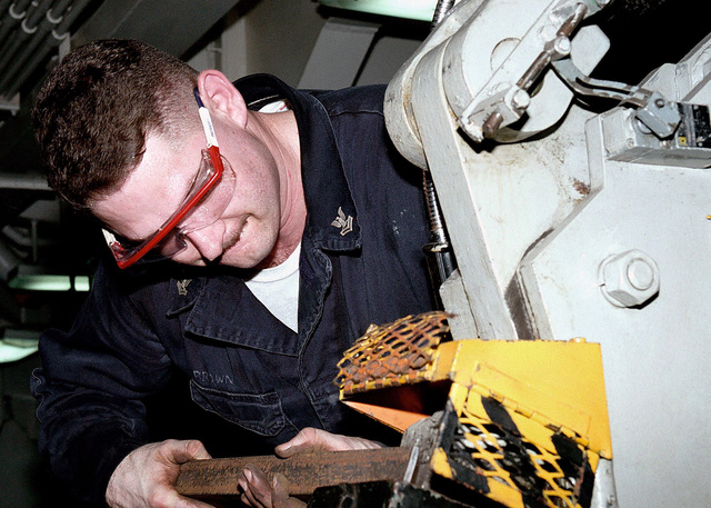 Hull Technician 2ND Class Brian Brown repairs the safety cage for a bomb hoist on board USS ABRAHAM LINCOLN (CVN 72). The ABRAHAM LINCOLN Battle Group is currently forward deployed to the Persian Gulf in support of United Nations sanctions against Iraq during Operation SOUTHERN WATCH