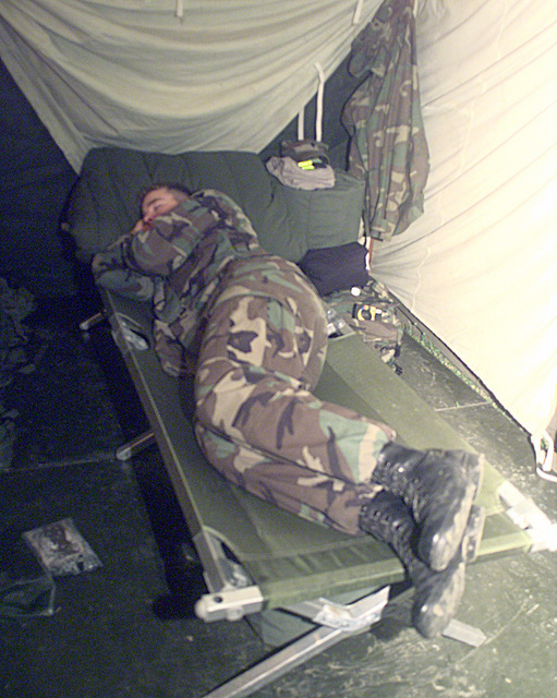 SPC Ryan Fales, a petroleum specialist, sleeps off a hard days work in his tent at Camp Hialeah in Pusan, Republic of Korea. Fales is attached to the 3rd Brigade 2nd Infantry Division from Fort Lewis, Washington. While in Korea, Fales will be working outside his military occupational specialty as a heavy wheeled vehicle operator in support of exercise Foal Eagle '98