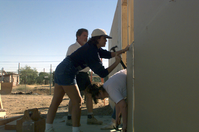US Air Force Captain Brenda Foster, 56th Medical Support Squadron staff pharmacist, secures a piece of drywall to the exterior of a house. The Company Grade Officers' Council along with the 56th Componet Repair Squadron volunteered their time and talents to the Habitat for Humanity to build houses for low-income families in Arizona