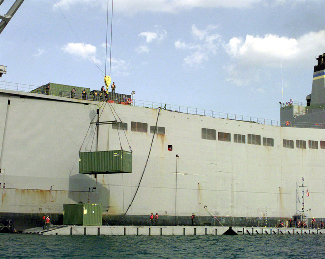 A Military Cargo Van is being lowered from the United States Naval Vessel POLLUX to waiting causeway ferries below on Oct. 18, 1998 during Exercise Foal Eagle in the Port of Pusan, Republic of Korea. The Causeway Ferry consists of a powered section made up of powered modules with internal propulsion and control components connectecd to non-powered modules