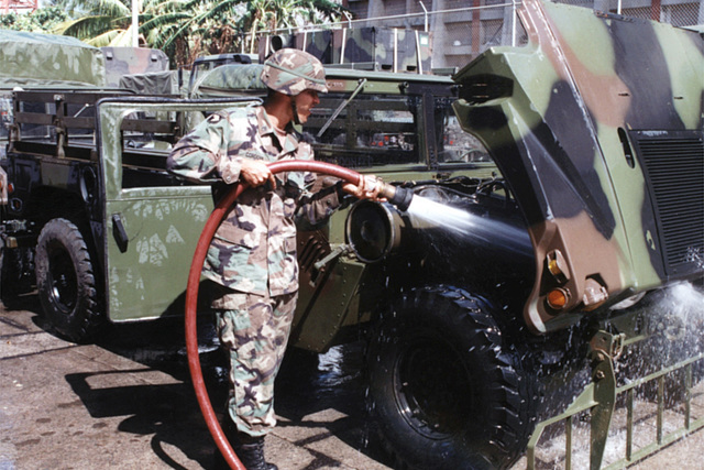 Following a field training exercise, a US Army soldier washes the engine compartment of a High-Mobility Multipurpose Wheeled Vehicle (HMMWV) at Fort Campbell, Kentucky