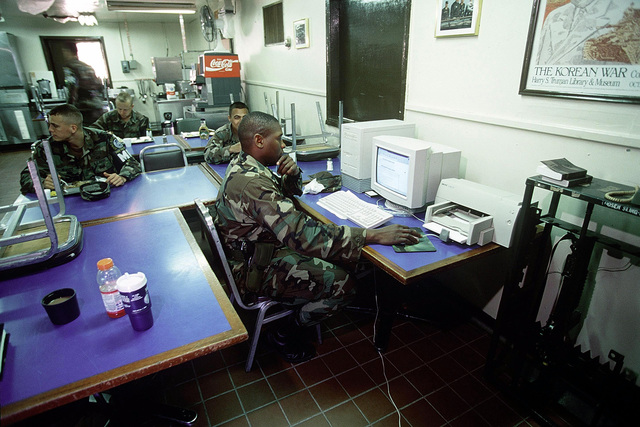 Members of the United Nations Command Security Battalion/Joint Security Area (UNSCB/JSA), eat lunch and check email while on duty at Observation Post Oullette (OPO), Oct. 20, 1998. In the event of an alarm, the platoon drops what they are doing and man their posts in a matter of seconds. The platoon practices alert procedures every day during the day and night. After being alerted the platoon heads to a central point where gear is gathered and orders for which bunker to man are given. (U.S. Air Force photo by SENIOR AIRMAN Jeffrey Allen) (Released)