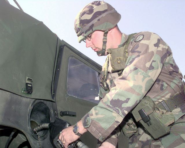 SGT Darrell Byerly refules a High-Mobility Multipurpose Wheeled Vehicle (HMMWV) at the heavy lift pad on Camp Carroll, Republic of Korea, on Oct. 23, 1998. Byerly, with other troops from the 20th Support Group, are operating the first fuel point and rest stop for the 2nd Infantry Division convoy heading to the northern part of South Korea in support of Foal Eagle '98. Foal Eagle is a deployment exercise that takes place once a year in Korea