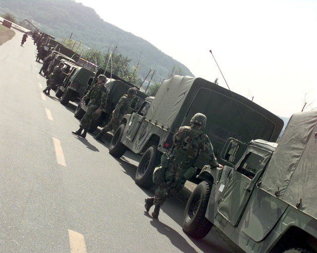 The 2nd Infantry Division convoy is parked as the soldiers walk about stretching their legs after a four hour drive, at the heavy lift pad on Camp Carroll, Republic of Korea, on Oct. 23, 1998. The 2nd Infantry Division convoy is utilizing their 1ST fuel and rest point, heading to the northern part of South Korea in support of Foal Eagle '98. Foal Eagle is a deployment exercise that takes place once a year in Korea