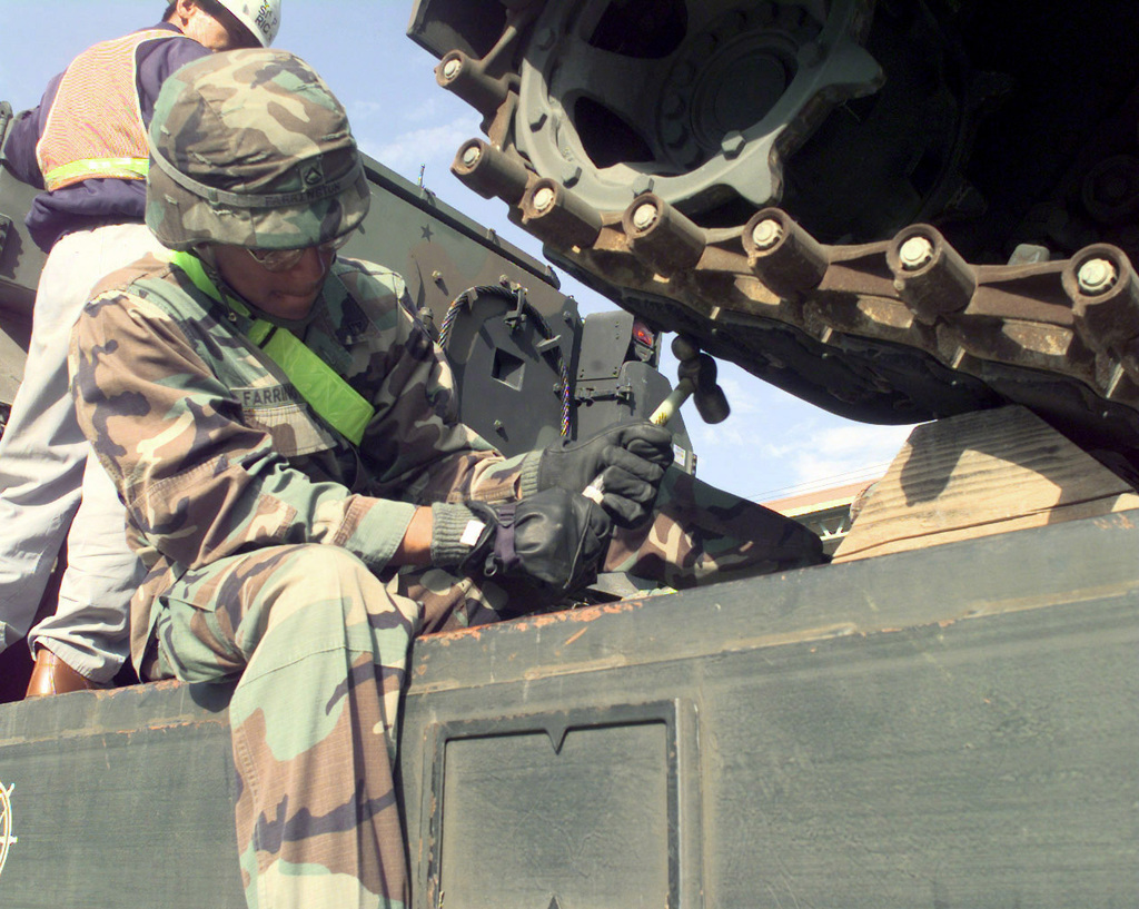 PFC Matthew Farrington nails a chalk block down while sling loading a M3/M4 Bradley Infantry Fighting Vehicle to a flat bed rail car at the Camp Carroll Rail Head in Korea, on Oct. 26, 1998. Farrington, of Bravo Company 1ST Battalion, 23rd Infantry, is a participant in a railhead exercise that will move the 23rd Infantry's equipment to Camp Casey in support of Foal Eagle '98. Foal Eagle is a field training exercise that takes place once a year in Korea