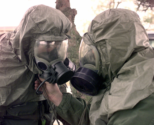 SSGT Mike Abbott (left), assigned to the 153rd Security Forces Squadron (SFS), Wyoming Air National Guard, has his mask tighten and adjusted by SRA Scott Humphries who is assigned to the 137th SFS, Peterson Air Force Base, Colorado, during a simulated chemical attack at Kunsan Air Base (AB), Republic of Korea, Oct. 28, 1998. Both are at Kunsan AB along with several other Air Force personnel participating in Foal Eagle '98