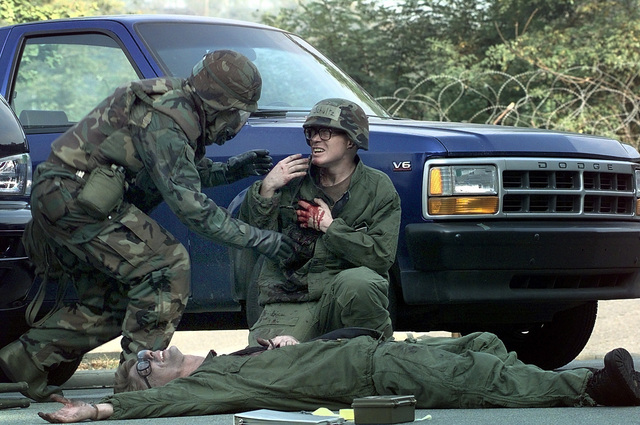 A US Air Force member of Osan Air Base, Republic of Korea, responds to several simulated shrapnel wounded airmen, during a Combat Employment Readiness Exercise held in conjunction with exercise Foal Eagle