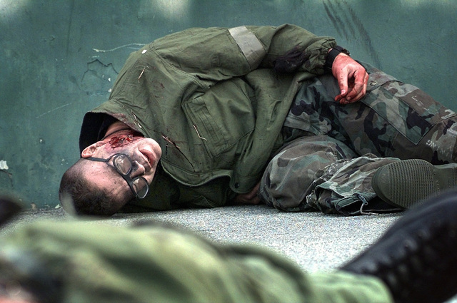 A US Air Force member of Osan Air Base, Republic of Korea, yells for help despite receiving a simulated shrapnel wound during a Combat Employment Readiness Exercise held in conjunction with exercise Foal Eagle '98
