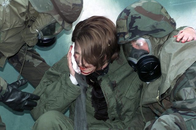 A1C Class Karen Jubenville, 303 Intelligence Squadron, Osan Air Base, Republic of Korea, simulating a facial shrapnel wound, is helped up and to an awaiting truck, during a Combat Employment Readiness Exercise held in conjunction with exercise Foal Eagle '98
