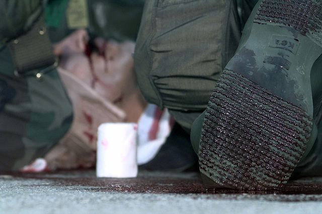 Imitation blood soaks the sole of a first aid giver as he attends to SRA Jose Rivera, 303 Intelligence Squadron, Osan Air Base, Republic of Korea, who acts unconscious after receiving a simulated shrapnel wound, during a Combat Employment Readiness Exercise held in conjunction with exercise Foal Eagle '98