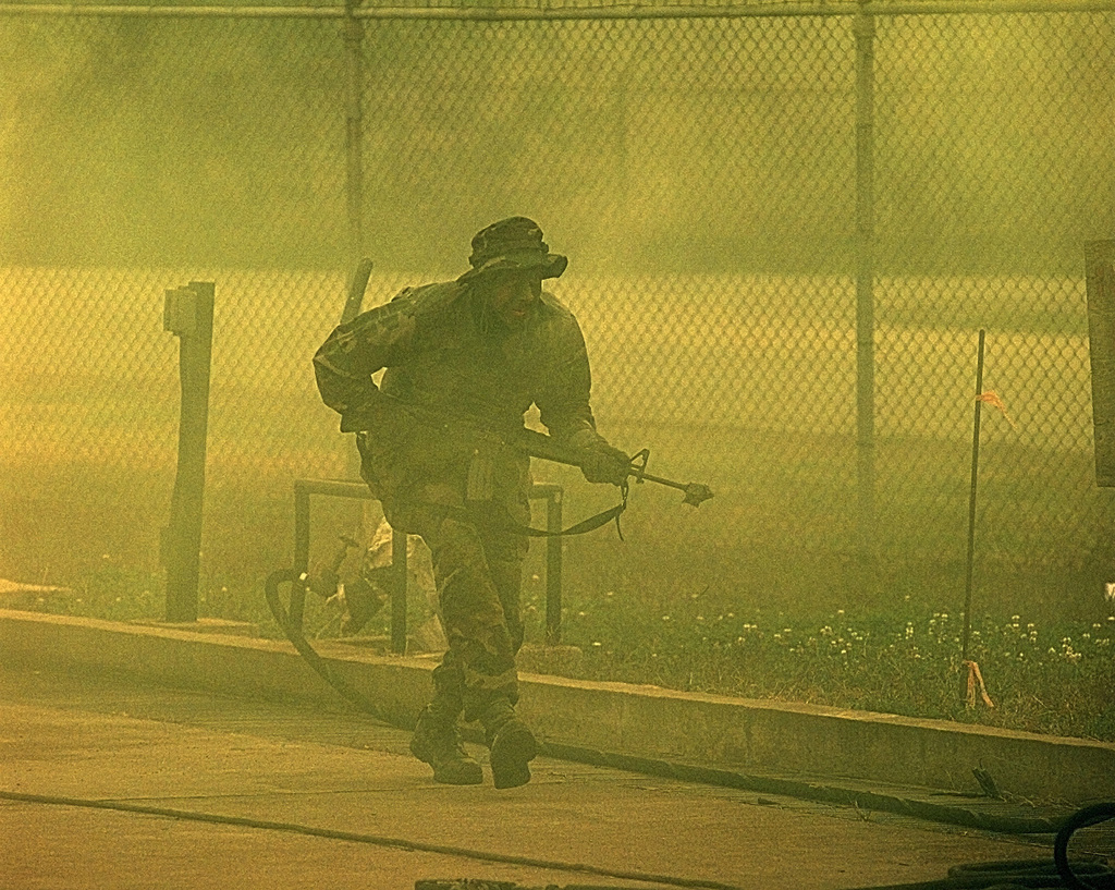 Members of 607th Combat Communications Squadron, Camp Humphries, Republic of Korea, role playing Opposing Forces (OPFOR), attack the Combat Communications Squadron compound during a Combat Employment Readiness Exercise (CERE), Oct. 30, 1998. During the exercise, simulated opposing Forces (OPFOR) attack the compound and try to destroy squadron assets
