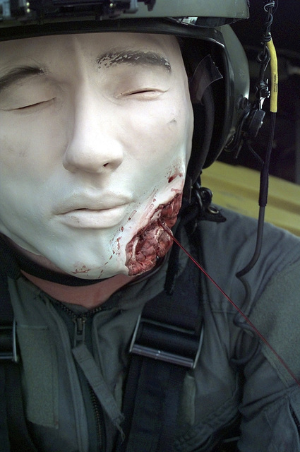 SSGT Greg Moody, UH-60 Blackhawk helicopter, gunner, 33rd Rescue Squadron, squirts blood out a face mask, to simulate head injuries. Members of the 33rd Rescue Squadron, Detetachment 1; 51st Civil Engineer/Fire department and 51st Medical Group, Osan Air Base, Republic of Korea, team up during a simulated emergency landing of a UH-60 Blackhawk helicopter. The landing, with fire, smoke, and all but one aircrew member injured, was simulated during a Combat Employment Readiness Exercise held in conjunction with exercise Foal Eagle