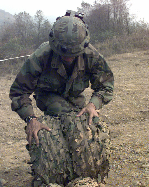 PFC Jong Staley rolls up a camouflage net at the Tactical Assembly Area Santa Barbara outside Wonapsan, Republic of Korea, Oct. 31, 1998. Staley is apart of the1st Battalion, 23rd Infantry Regiment from the 3rd Brigade, 2nd Infantry Division from Fort Lewis, Washington. The 3rd Brigade is in Korea as part of Foal Eagle '98, a combined exercise involving the Republic of Korea Army and the United States Armed Forces