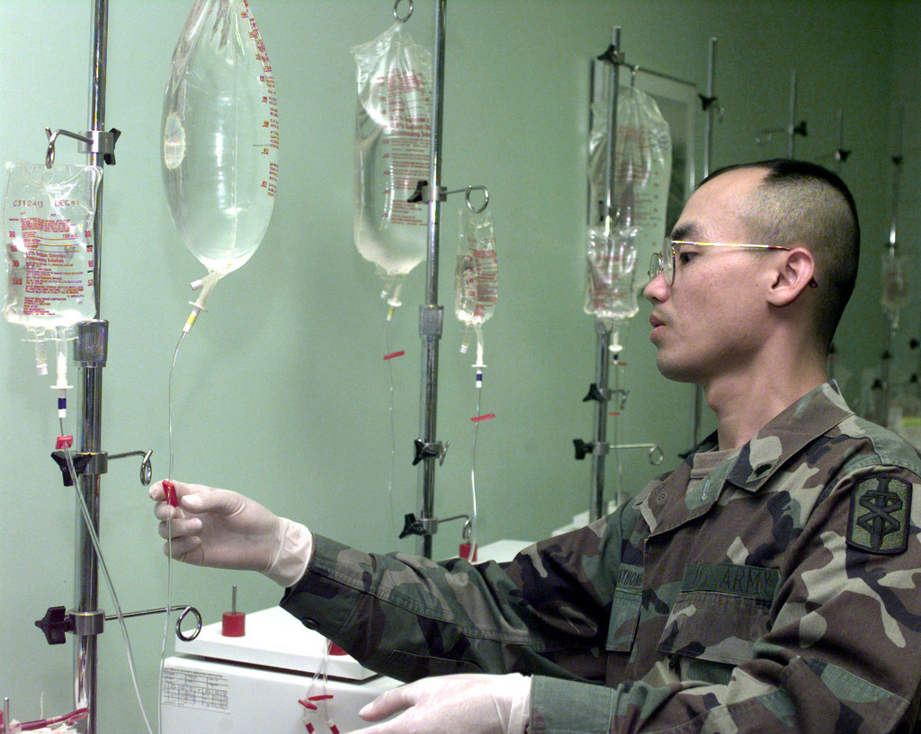 SPC Vilayphone Sisouphanthong pinches a wash line while operating a blood processing machine at the Camp Carroll Frozen Blood Depot in Republic of Korea, Nov. 1, 1998. Sisoupanthong, of Alpha Company, 16th Medical Logistics Battalion, is preparing to send blood to a battlefield exercise in support of Foal Eagle '98. Foal Eagle is a deployment exercise that takes place once a year in Korea