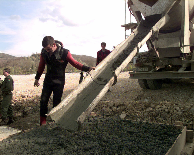 Straight on medium shot as members of the Hungarian Engineering Contingent, pour cement into a barrier. The top portion of the barrier will be welded to the legs of the bridge (Not shown) so the bridge does not shift. Supply routes (Not shown) for Stabilization Force Personnel, have to be in good condition to allow the freedom of movement in Bosnia-Herzegovina. A bridge near the construction site located in Doboj, Bosnia was downgraded due to excessive traffic flow. The solution is the Maybe and Johnson bridge