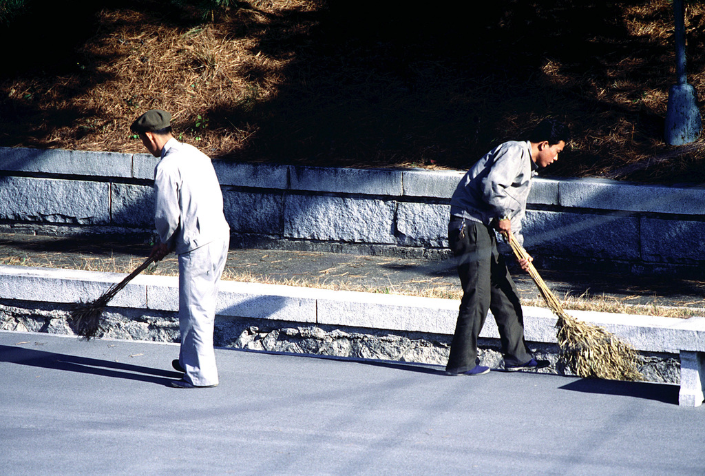 Workers from the Democratic Peoples Republic of Korea (DPRK), also, North Korea, use wide mustache brooms to sweep an area where nine caskets will be delivered on the DPRK side of the Demilitarized Zone (DMZ) for a repatriation ceremony at the Panmunjom Joint Security Area