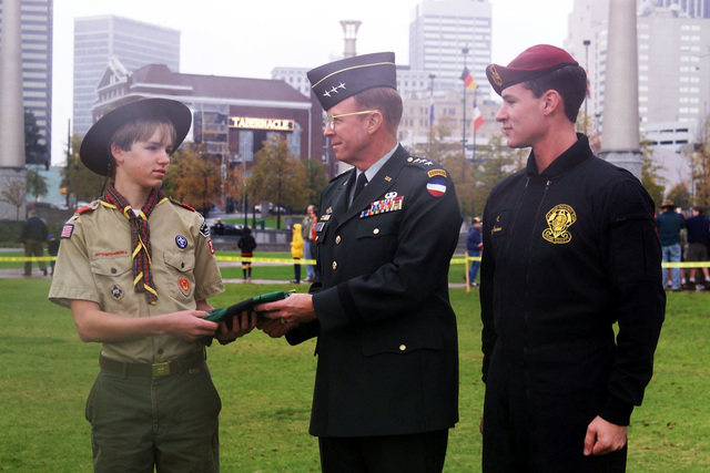 US Army Lieutenant General John M. Pickler (Center), CHIEF of STAFF, Forces Command, Fort McPherson, Georgia, receives a flag from a selected member of the Boy Scouts of America as a team member from the Army's Golden KNights Parachute Team stands by to recieve it to commemorate the Team's jump into Centennial park in downtown Atlanta, GA., as part of the Atlanta Council Boy Scout Show
