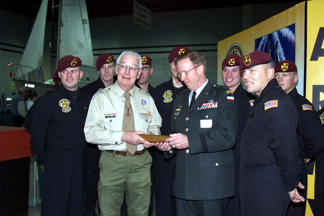 US Army Lieutenant General John M. Pickler (In Dress Green uniform), CHIEF of STAFF, Forces Command, and the US Army's Golden KNights Parachute Team present John Langford, Atlanta, Georgia, Boy Scout Council Commissioner, a momento to mark their performance at the Boy Scout Show