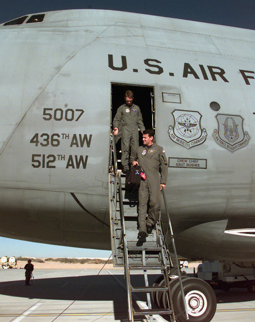 Lieutenant Colonel Frank Padilla, Commander 312th Airlift Squadron, and First Lieutenant Pete Gross, exit a C-5 Galaxy after landing at Biggs Army Air Field at Fort Bliss in El Paso, Texas. The C-5 landed at Biggs Army Air Field to pick up troops and equipment for transport to Southwest Asia