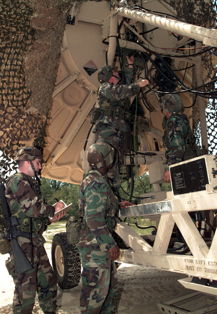 First Lieutenant Richard Tuggle, Military Occupational Specialty (MOS) 31S [ Satellite Communications Systems Operator-Maintainer], 235th Signal (Sig) Company 63rd Sig Bn, 93rd Sig Bde, supervises members of satellite team hooking up an OE-361 (20 ft) Quick Reaction Satellite Antenna (QRSA)