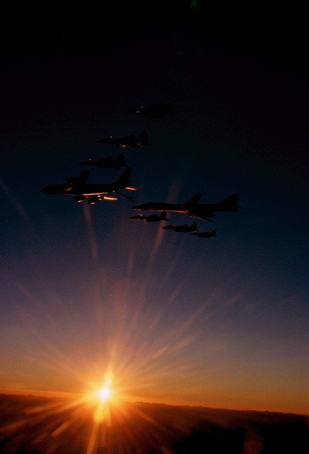 """Aerial view from a low angle up at a flight of various aircraft made up of one USAF KC-135 Stratotanker, four USAF F-15 Eagles, two USAF F-16 Falcons and a USAF B1-B Lancer getting refueled by the KC-135. The sun sets along the horizon as these aircraft, assigned to the 366th Wing's """"Gunfighters"""" from Mountain Home Air Force Base, Idaho, fly a training sortie over the Cascade Mountain range. From the top: F-16J, F-15E, F-15C, KC-135R, B1-B, F-15C, F-15E, F-16CJ"""