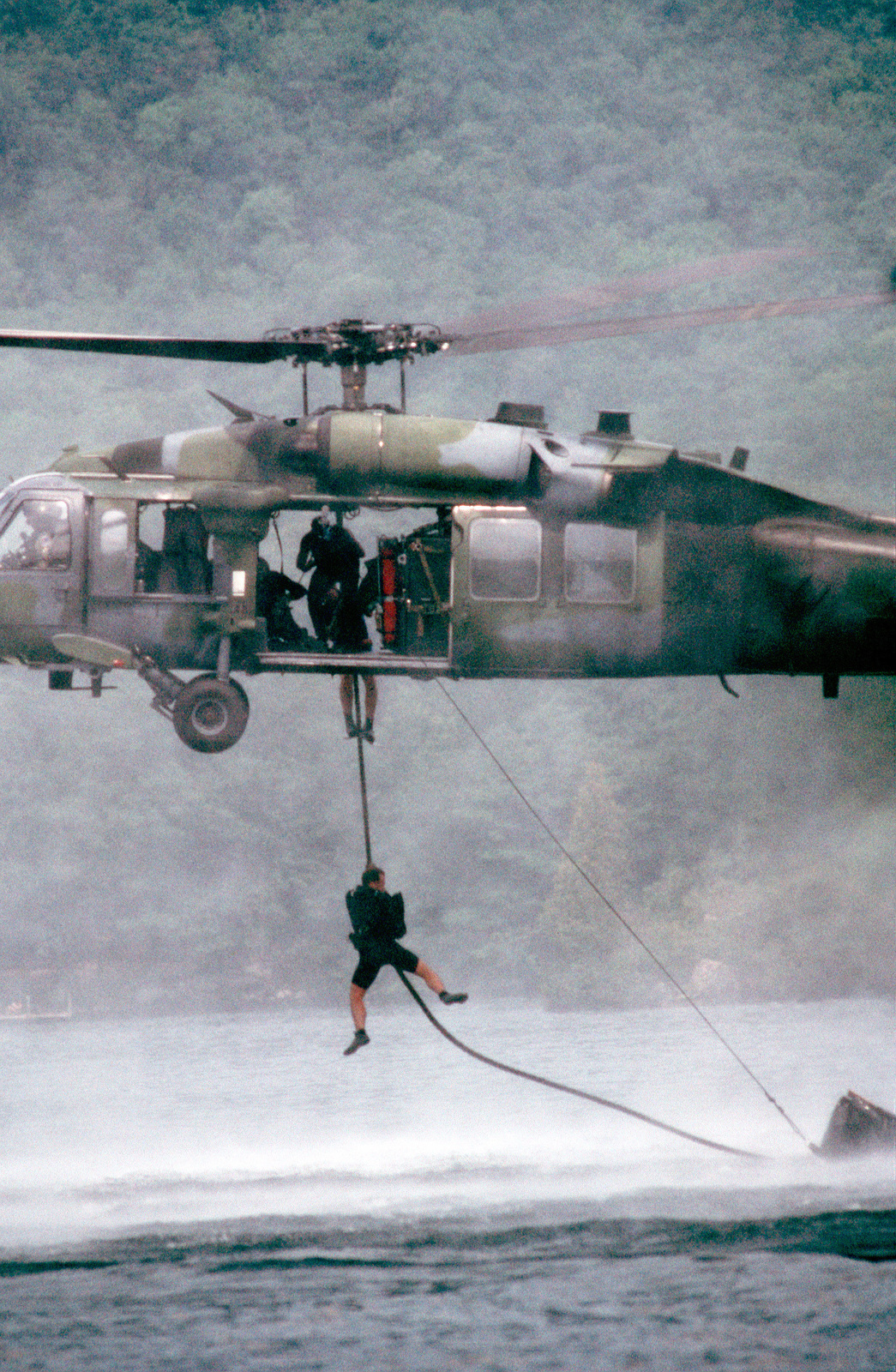 """Left side medium shot of a USAF HH-60 Pave Hawk Combat Rescue Helicopter as a pararesuemen from the 102nd rescue Squadron fastrope into Lake George, New York, during """"waterworks"""" training"""