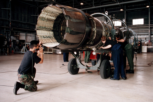 Shot of USAF SENIOR AIRMAN Robert Navarro (Left), AIRMAN First Class Kristin Coates and STAFF Sergeant Ching Foster, all from the 31st Maintenance Squadron, Aviano Air Base, Italy, inspect a F-16 engine