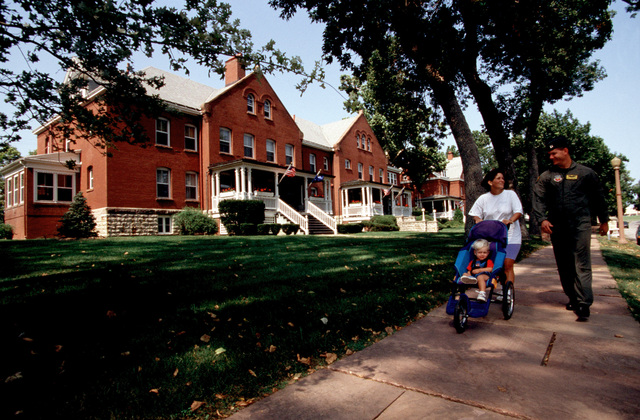 Straight on medium shot of USAF Captain Brian Humphrey of the 45th Reconnaissance Squadron, his wife, Theresa, and son Justin as they enjoy a stroll along the historic housing on Offutt Air Force Base, Nebraska