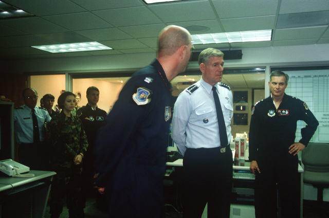 US Air Force Captain Rolf Boettger, Crew Commander of AFSPACE SOC, explains the role of the Space Operations Center (SOC) pertaining to combat operation duties to General Richard B. Myers as Major General Gerald Perryman, Commander of the 14th Air Force, looks on