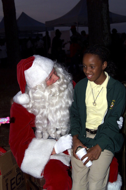 US Army Sergeant First Class Jimmie Sutterfield, Director of Plans, Training, Mobilization and Security at Fort McPherson, Georgia, plays Santa Claus and listens to the Christmas request of a young lady at the Fort Gillem, GA, Christmas Tree Lighting