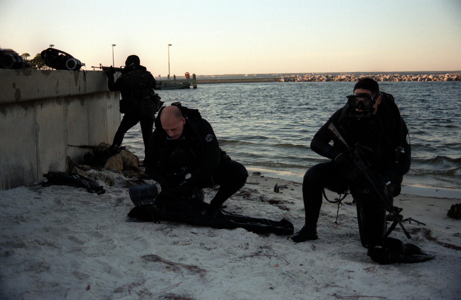 STAFF Sergeant Thomas (background), of 2D Reconnaissance Battalion posts security while other divers take off their dive equipment. The 2D Reconnaissance Marines have been deployed to Hurlbert Field, Flordia, for two-week long dive/land maneuvers training exercise. They are armed with 5.56mm Colt M16A2 Assault Rifle and are using the LAR-V Closed Circuit Rebreather
