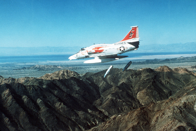 An air-to-air left side view of a Marine A-4M Skyhawk aircraft dropping two napalm canisters over a mountain area. The A-4M is from Marine Attack Training Squadron 102 (VMAT-102)
