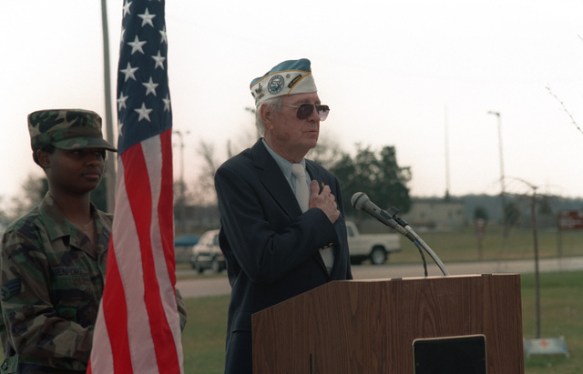 During the Annual Pearl Harbor memorial ceremony at Dover AFB, James Beuter, a Pearl Harbor Survivor, leads the assembly in the Pledge of Allegiance to the United States of America