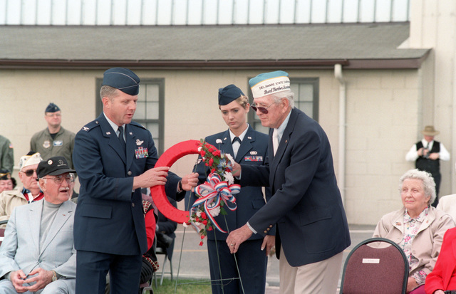 US Air Force SENIOR AIRMAN Wendy Brabender from the 436th Services Squadron, hands off the memorial wreath to Felix M. Grieder, 436th Airlift Wing Commander and Benjamin Bowings, Pearl Harbor survivor as Retired General Fred Vetter, former 436th Airlift Wing Commander looks on. Ceremony held at the AMC Museum at Dover AFB