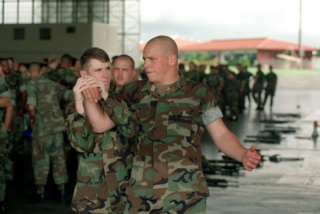 Lance Corporal Charles Ostrand of 2D Light Armored Reconnaissance Battalion, First Platoon/Third Squad, takes time out of a joint crowd-control demonstration to train an airman of the 24th Security Forces Squadron in the tactics of hand-to-hand combat inside a hangar at Howard Air Force Base, Panama. The Marine are serving as Security Force detachment at the Camp Hayes compound situated on the shoreline of the Panama Canal