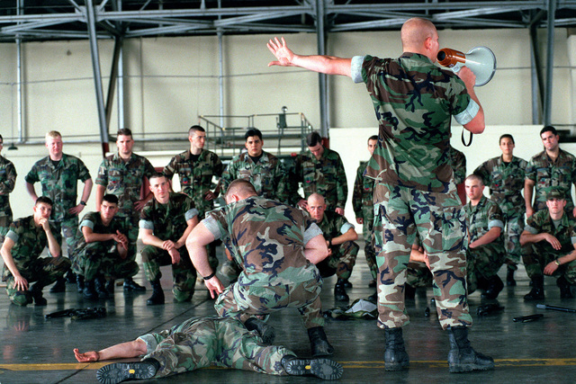 Lance Corporal Charles Ostrand of 2D Light Armored Reconnaissance (LAR) Battalion, First Platoon/Third Squad, takes time out of a joint crowd-control demonstration to train airmen of the 24th Security Forces Squadron in the tactics of apprehending an assailant. Ostrand is using fellow Marines of 2D LAR Battalion, Sergeant (SGT) Wesley Dinsmore (face down) and SGT Donald Markham (kneeling) as demonstrators. They are inside a hangar at Howard Air Force Base, Panama