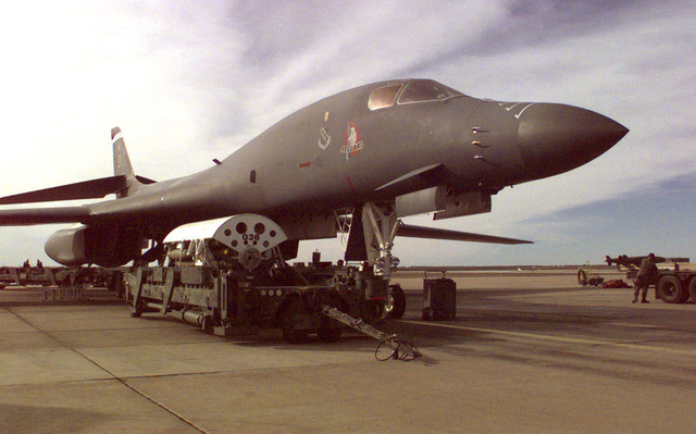 A conventional bomb module (CBM) with MK-82 bombs sits on a loader before being loaded into one of the bomb bays of the B-1B Lancer in preparation for a mission to support DESERT FOX