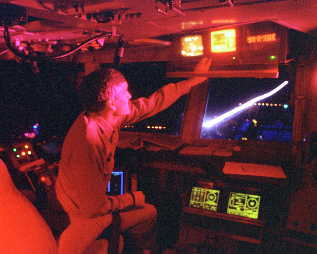 CAPT Marty Chanik, commanding officer of the USS ENTERPRISE (CVN-65), monitors the first wave of strike aircraft as the afterburner from an F/A-18 Hornet lights up the night sky as it launches from the carrier's flight deck in support of DESERT FOX