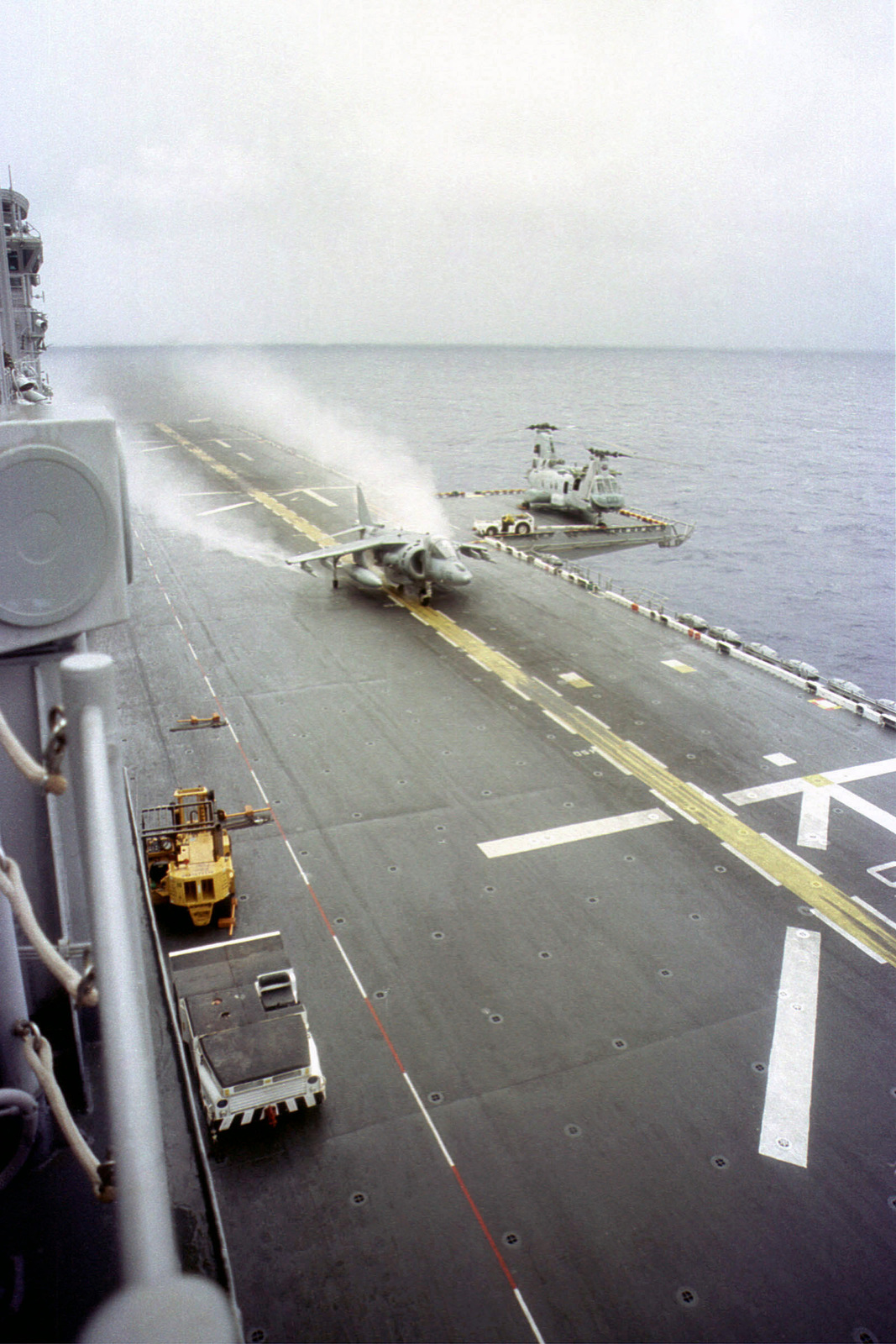 A US Marine Corps AV-8B Harrier from Marine Medium Helicopter Squadron 364 (Reinforced) (HMM-364), 13th Marine Expeditionary Unit (MEU), Special Operations Capable (SOC) takes off from the flight deck of the USS BOXER (LHD 4) during routine flight operations. A CH-46E Sea Knight is parked on elevator. Western Pacific deployment, WestPac 99-1