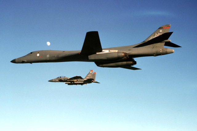 Aerial view, medium shot looking up at a USAF B1-B Lancer being escorted by a F-15E Eagle. This image is from the January 1999 edition of AIRMAN Magazine highlighting the Expeditionary Aerospace Force