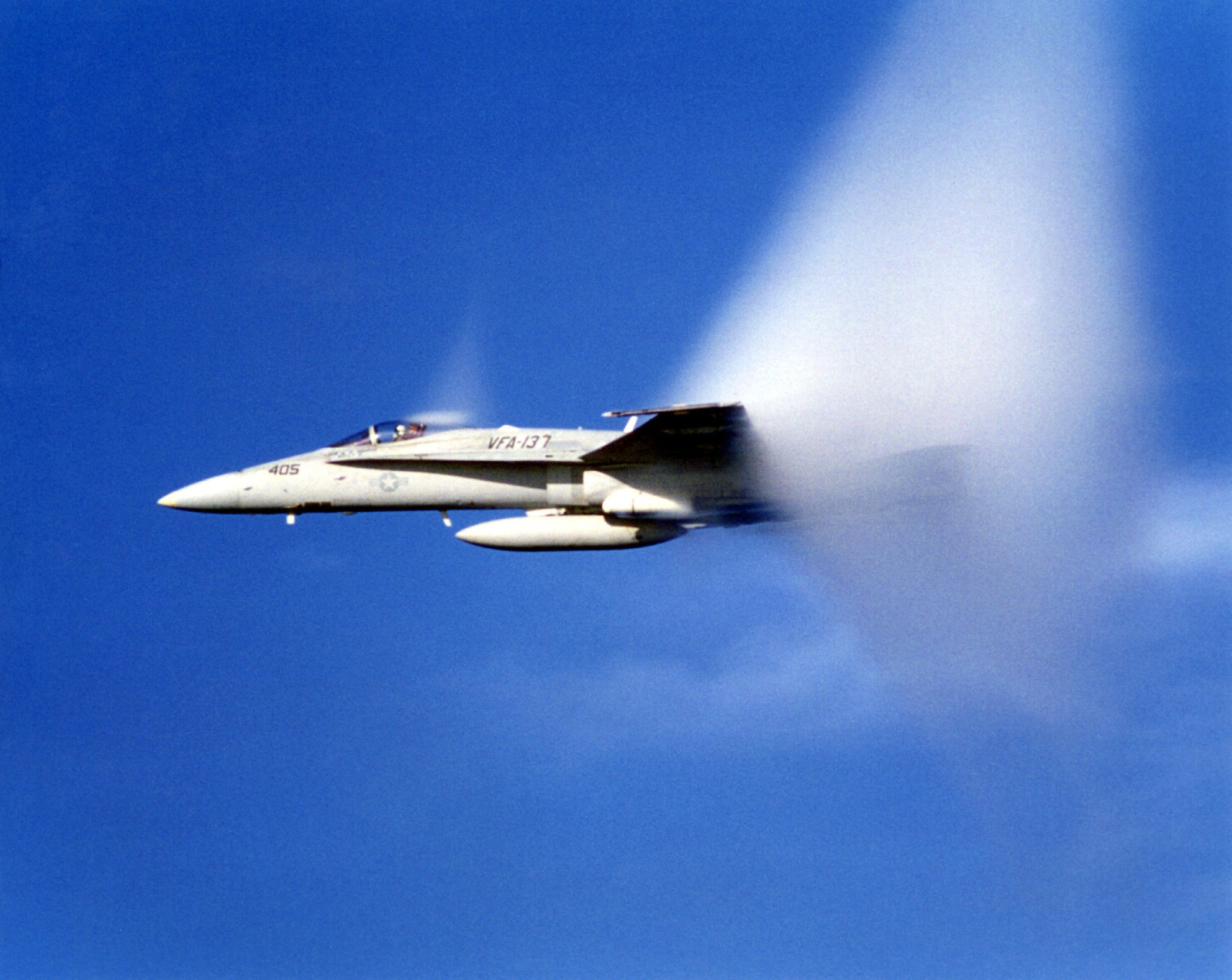 An F/A 18 Hornet from Strike Fighter Squadron 137 (VFA-137) flies faster than the sound, creating a sonic boom and a visual mist during an exercise off the coast of San Diego, California. Exact Date Unknown