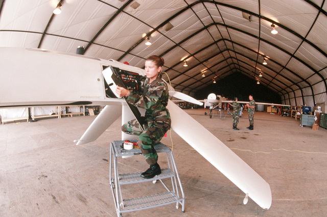 An unidentified USAF AIRMAN First Class performs maintenance on a Predator, Unmanned Aerial Vehicle inside a hangar. This image is from the January 1999 edition of AIRMAN Magazine highlighting the Expeditionary Aerospace Force