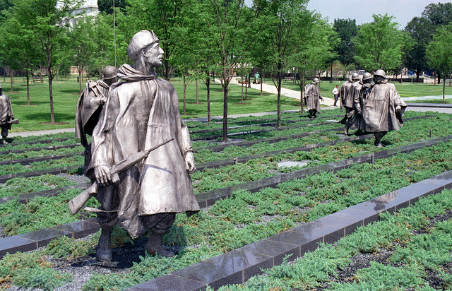 In the triangular field of service of the Korean War Veterans Memorial, located on the National Mall near the west end of the Reflecting Pool, 19 stainless steel statues depict a squad on patrol. The figures represent members of the Air Force, Army, Marines, and Navy from a variety of ethnic backgrounds. The strips of granite and scrubby juniper bushes suggest the rough terrain and the windblown ponchos suggest the harsh weather encountered. Exact Date Shot Unknown