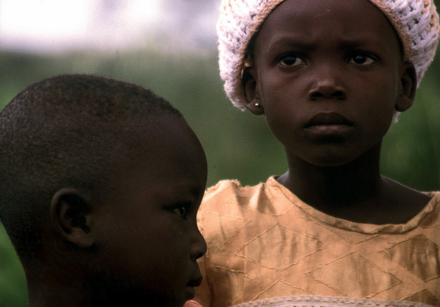 """Military Photographer of the Year Winner 1999 TITLE: """"Looking Ahead"""" CATEGORY: Portfolio PLACE: Third Place Portfolio CAPTION INFORMATION: Children in Dominasi Village, Ghana, watch as their standard of living improves. U.S. Navy and Marine volunteers traveled deep into the country, to a village, where military troops have never been seen, to help villagers build new homes. The homes, made of mud bricks, are paid for by Habitat for Humanity, which works in 15 countries in Africa trying to improve the quality of life for thousands of people. IMAGE FILE #DD-SP-01-00053"""