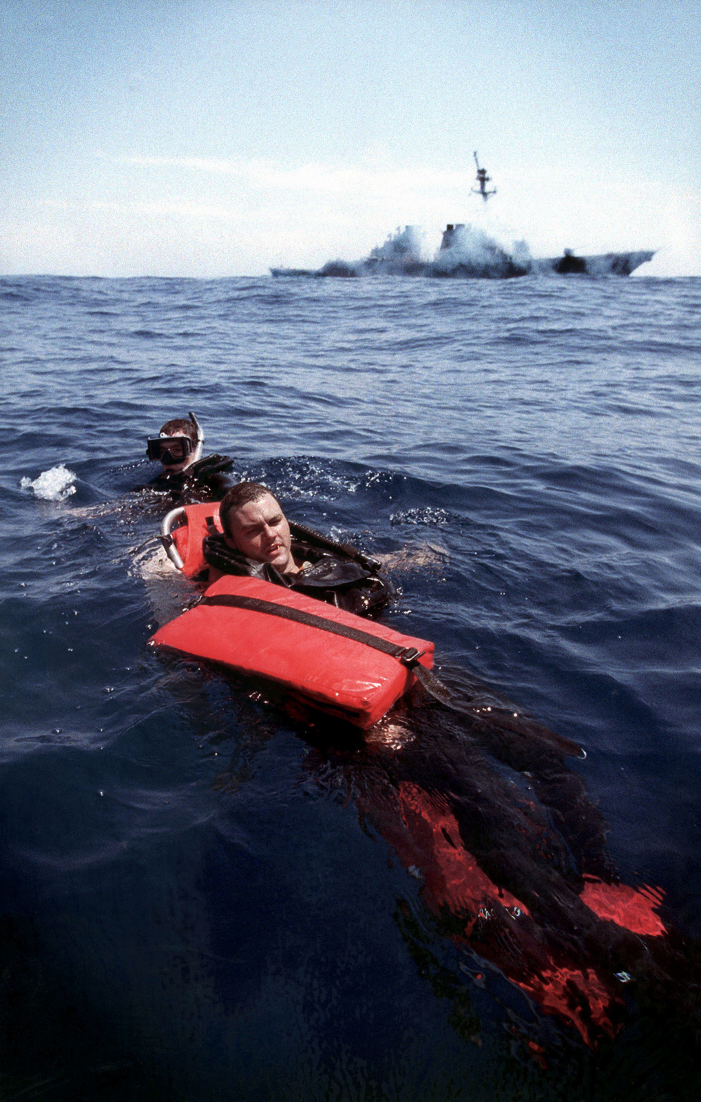 """Military Photographer of the Year Winner 1999 TITLE: """"Search and Rescue"""" CATEGORY: Portfolio PLACE: Third Place Portfolio CAPTION INFORMATION: USS Barry DDG 52, homeport Norfolk, Virginia, August 3, 1999. Search and rescue swimmer OS2 J.P. Powell practices strapping BM3 Henry Taylor to a stretcher and pulling him to safety, during a man overboard drill. Such drills are frequent due to the resent loss of a crewman on one of the Norfolk based aircraft carriers. IMAGE FILE #DD-SP-01-00055"""