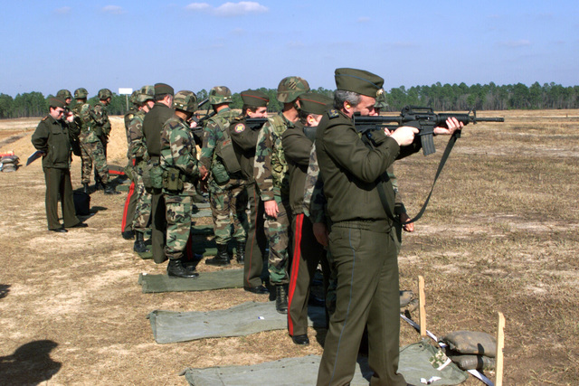 General Lieutenant Vasily Mikhailovich Zavgorodny, Deputy CHIEF of STAFF, Directorate of General STAFF, Russian Military (2nd in line w/striped pants), And his entourage fire small arms at the Mulitpurpose Range Complex (MPRC) at the US Army Training and Support Center, Fort Stewart, Georgia. The Russian Soldier in the foreground fires the US made M16 Rifle