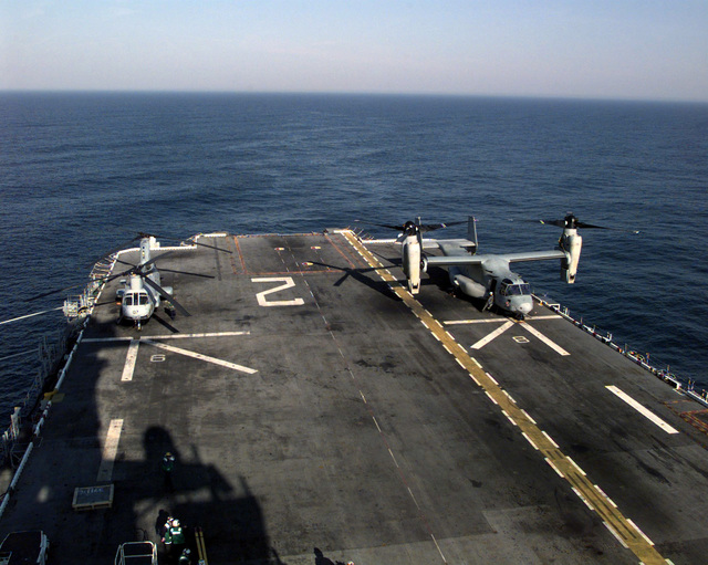 A V-22 Osprey sits beside a CH-46 Sea Knight helicopter on the USS SAIPANs (LHA 2) flight deck