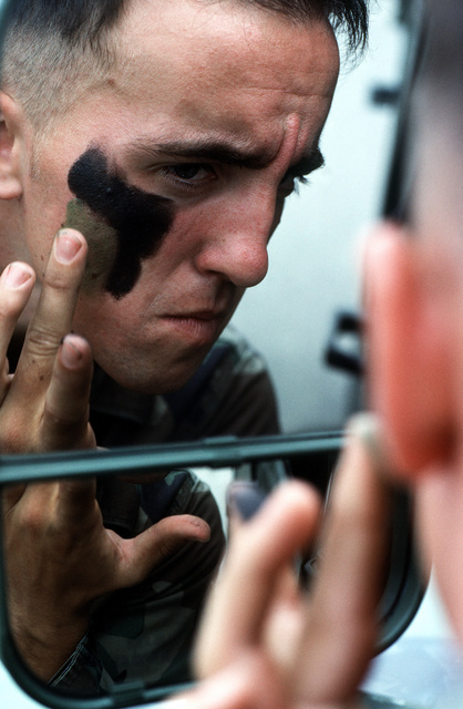 """AIRMAN First Class Ryan Stannard as he """"cammies"""" up his face using the mirror of his High-Mobility Multipurpose Wheeled Vehicle (HMMWV). AIC Stannard is a terminal attack controller stationed with an Army unit at Camp Humphreys, Republic of Korea. He says he likes his job because of the unique mission and lifestyle controllers lead"""