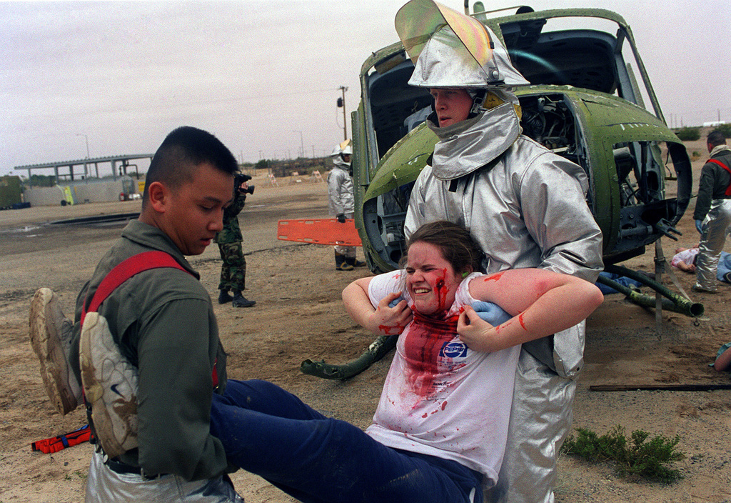 Two Marines from Crash Fire Rescue (CFR), Lance Corporal Dean A. Young (right) and Lance Corporal Anthony W. Iglesias (left), carry a young girl (from Yuma High School), to a secure location.  Community role players participated in the Mass Casualty Drill aboard Marine Corps Air Station Yuma as casualties.  Young is in an aluminized Proximity Suit and his helmet has a gold face shield and a modified aluminized shroud to protect neck area